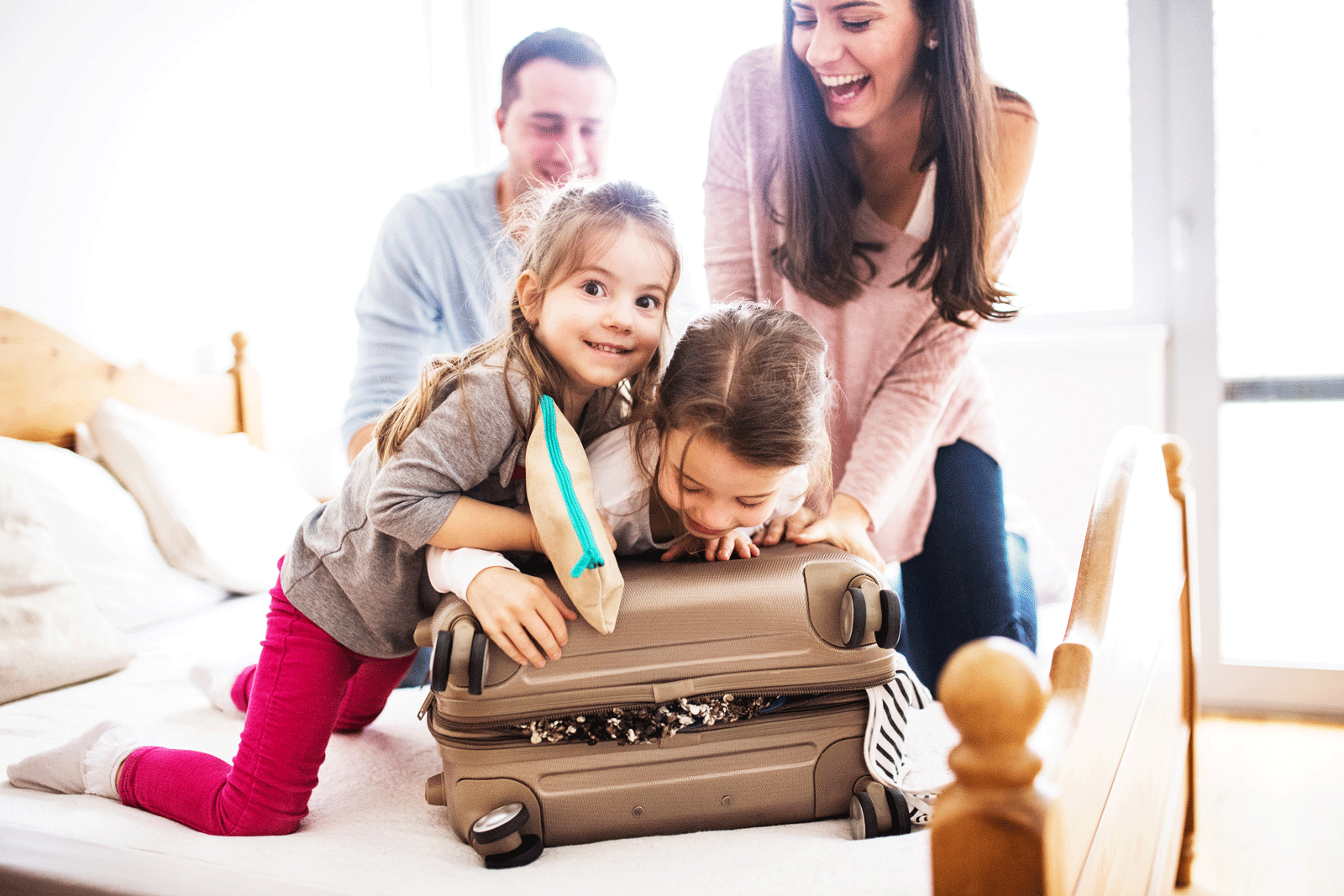 Family with young kids packing a suitcase